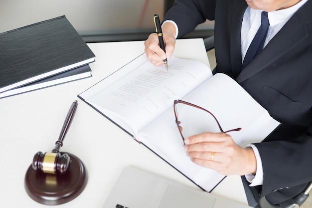 Prawnik strony pisze dokument w sądzie (sprawiedliwość, prawo) z blokiem dźwiękowym