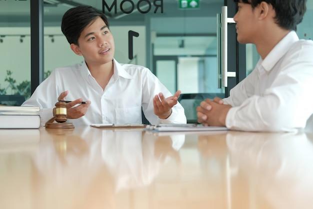 Prawnik udziela rad człowiekowi. biznesmen omawianie przepisów prawnych w kancelarii prawnej. posiedzenie zespołu sędziego na sali sądowej