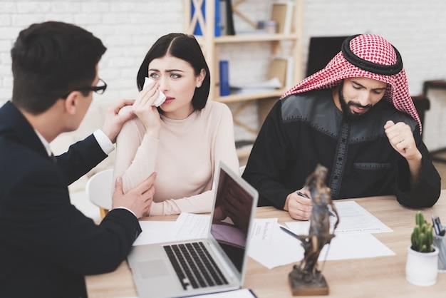 Prawnik w biurze z arabską parą. pociesza kobietę.