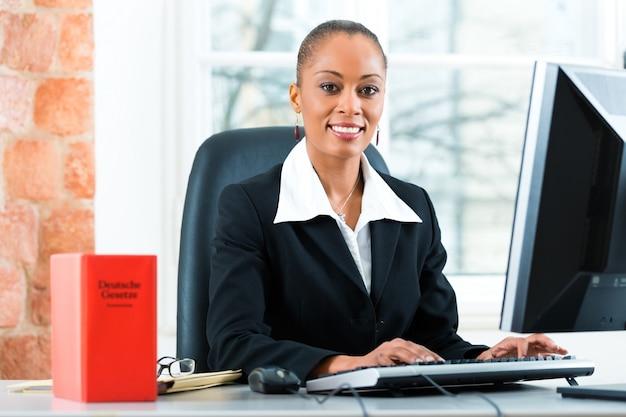 Prawnik w swoim biurze z książką prawa na komputerze