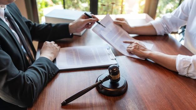 Prawnik współpracujący z klientem omawiający dokumenty kontraktowe ze skalą mosiężną