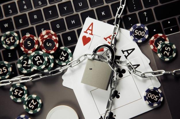 Prawo i zasady dotyczące koncepcji hazardu online, kłódki i kart do gry na klawiaturze laptopa.