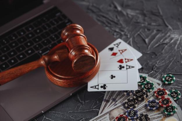 Prawo i zasady dotyczące koncepcji hazardu online, sędzia młotek z kartami do gry i banknotami pieniędzy na klawiaturze laptopa.