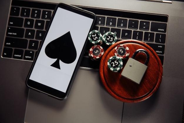Prawo i zasady dotyczące koncepcji hazardu online, smartfona z kłódką i żetonami do gry na klawiaturze.
