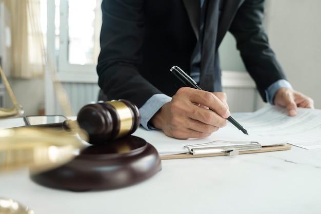 Prawo, usługi prawne, doradztwo, pojęcie sprawiedliwości i prawa. mężczyzna prawnik w biurze z mosiężną skalą.