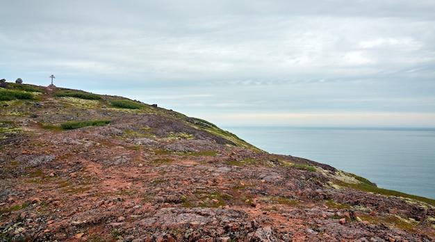 Prawosławny krzyż na skalistym wybrzeżu morza barentsa, półwysep kolski, rosja
