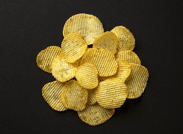 Prążkowane chipsy ziemniaczane na czarnym tle