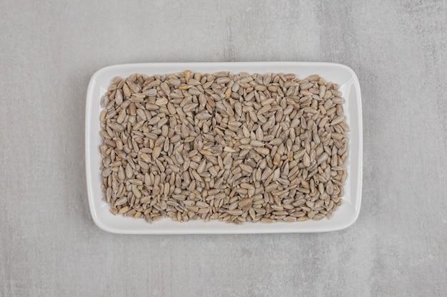 Prażone nasiona słonecznika na białym talerzu.