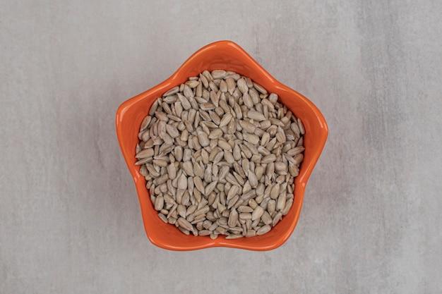 Prażone nasiona słonecznika w pomarańczowej misce.