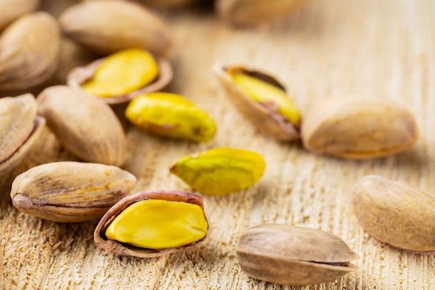 Prażone orzeszki pistacjowe. smażone i słone pistacje na drewnianym tle. zbliżenie