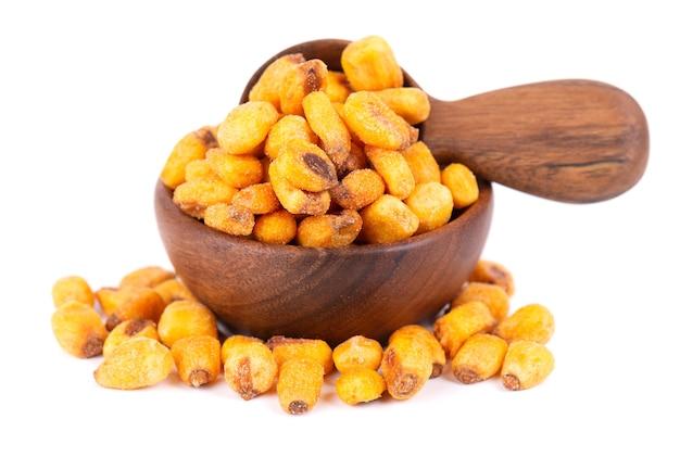 Prażone solone orzechy kukurydziane w drewnianej misce i łyżką, na białym tle. przekąska piwna, sucha kukurydza z przyprawami.