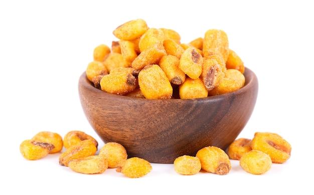 Prażone solone orzechy kukurydziane w drewnianej misce, na białym tle. przekąska piwna, sucha kukurydza z przyprawami.