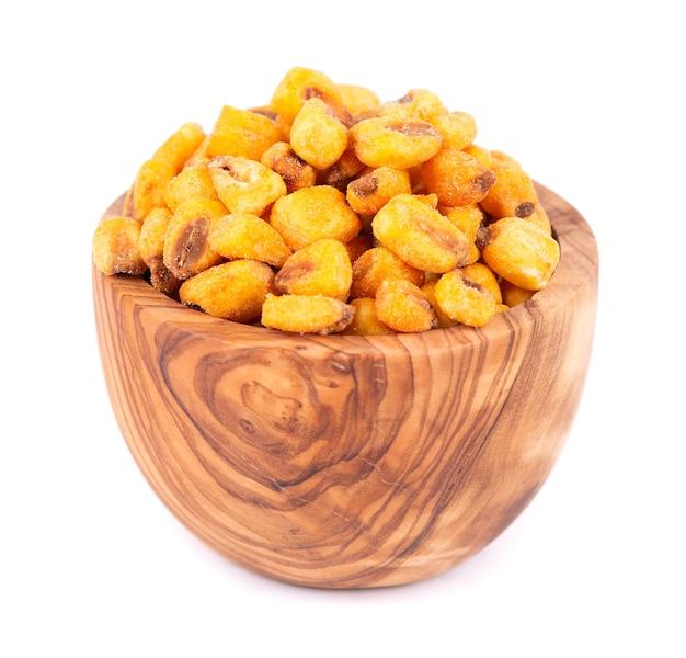Prażone solone orzechy kukurydziane w oliwnej misce, na białym tle. przekąska piwna, sucha kukurydza z przyprawami.