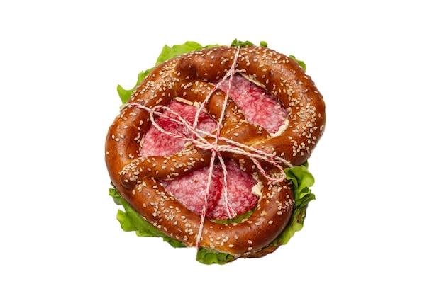 Precel z salami i sałatą na białym tle na białej powierzchni. smaczna przekąska.