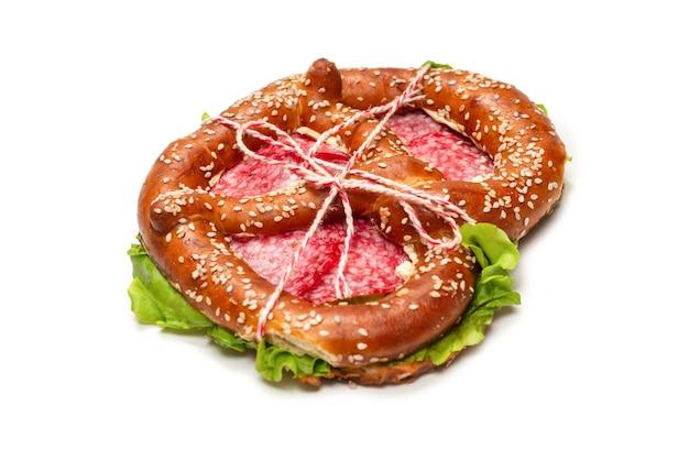 Precel z salami i sałatą na białym tle. smaczna przekąska.