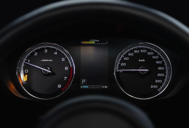 Prędkościomierz, obrotomierz i prędkościomierz na kierownicy nowoczesnego samochodu ze zintegrowanym wskaźnikiem poziomu paliwa w zbiorniku z białymi strzałkami
