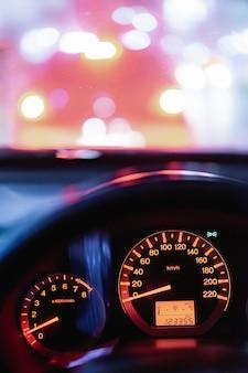 Prędkościomierz w nowożytnym pojazdu samochodu przejażdżki podróży wycieczce samochodowej w nocy mieście z plamy bokeh światła ruchu