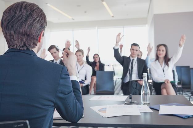 Prelegent na konferencji biznesowej i publiczność zadająca pytania