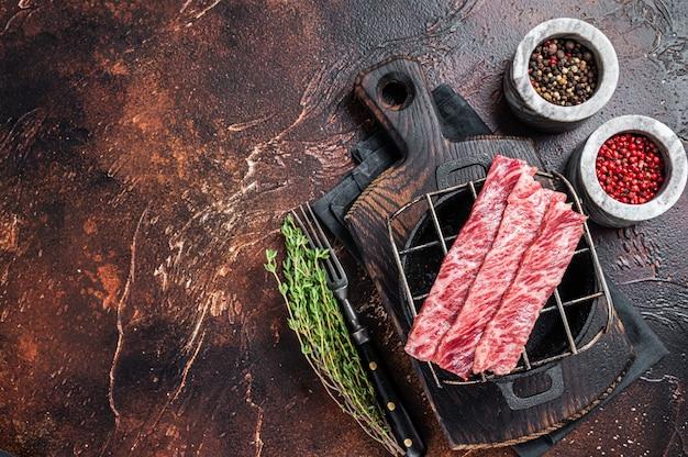 Premium surowa pokrojona wołowina wagyu a5 steki na grillu do yakiniku. japońskie potrawy. ciemne tło. widok z góry. skopiuj miejsce.