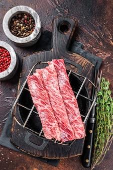 Premium surowa pokrojona wołowina wagyu a5 steki na grillu do yakiniku. japońskie potrawy. ciemne tło. widok z góry.
