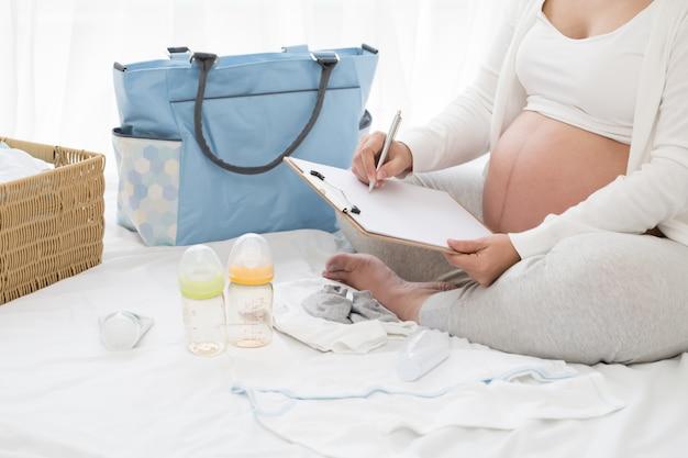 Prenatalne kobiety w ciąży planujące kalendarz i listę kontrolną dla dziecka, przygotowywanie przyborów do ciąży