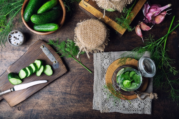 Preparat do kiszenia ogórków. domowe ogórki pokrojone w plastry z koperkiem i czosnkiem na rustykalnym drewnianym stole. zbieranie warzyw na zimę. widok z góry.