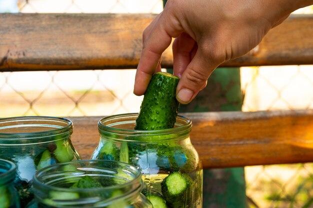 Preparat do konserwowania ogórków na zimę, kobieta układa składniki w słoiku z bliska.