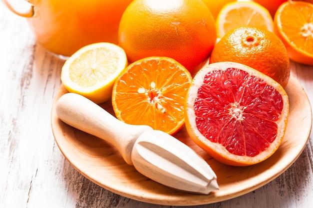 Preparat na sok cytrusowy na śniadanie. drewniany rozwiertak do cytrusów z owocami.