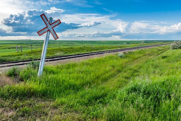 Preryjny kolejowy skrzyżowanie znak i ślada z burz chmurami na horyzoncie w saskatchewan, kanada