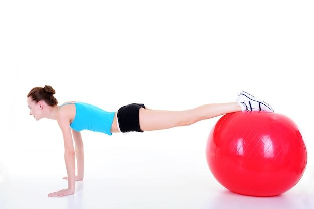 Press-up młodej dziewczyny przy użyciu fitball