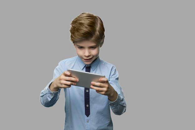 Preteen boy gra w grę na smartfonie. podekscytowany dziecko grając w gry wideo na telefonie na szarym tle. młodzież, technologia, styl życia.