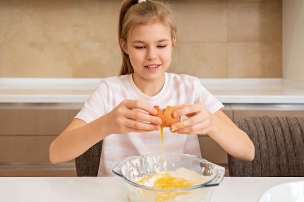 Preteen dziewczyna łamie jajko w misce na stole, gotując w kuchni
