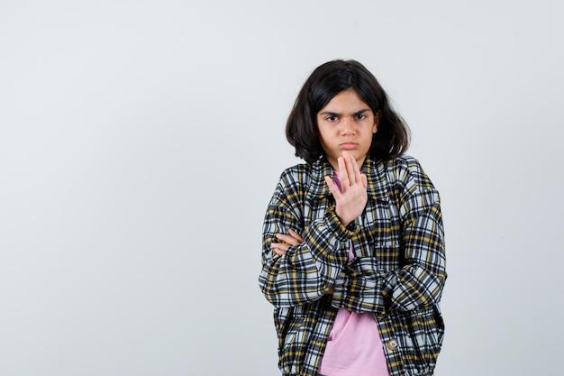 Preteen dziewczyna odrzuca coś w koszuli, kurtce i wygląda na obrażoną. przedni widok. miejsce na tekst
