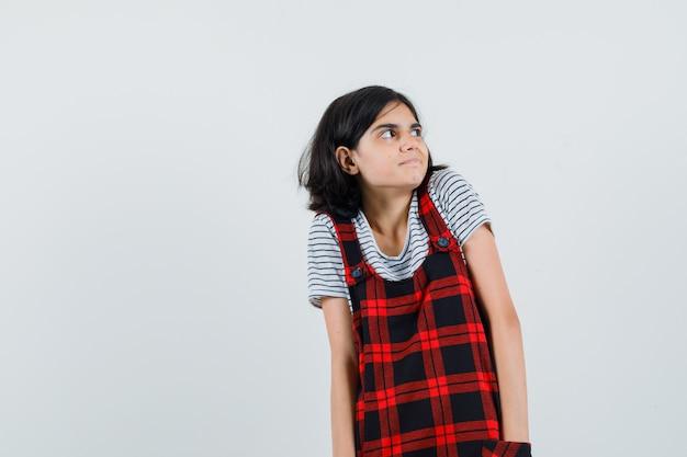 Preteen dziewczyna patrząc w nieoczekiwany sposób na bok w koszulce