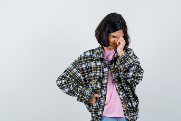 Preteen dziewczyna pociera jedno oko w koszulę, kurtkę i wygląda na senną, widok z przodu.