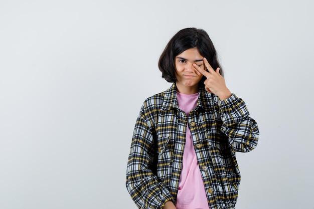 Preteen dziewczyna pociera jedno oko w koszulę, widok z przodu kurtki. miejsce na tekst