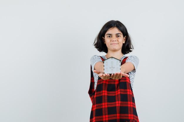 Preteen dziewczyna pokazująca modelowy dom w koszulce, kombinezonie