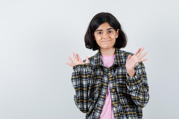 Preteen dziewczyna pokazuje bezradny gest w koszuli, kurtce, widok z przodu.