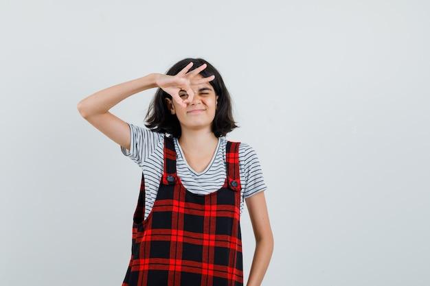 Preteen dziewczyna pokazuje ok gest na jej oku w t-shirt