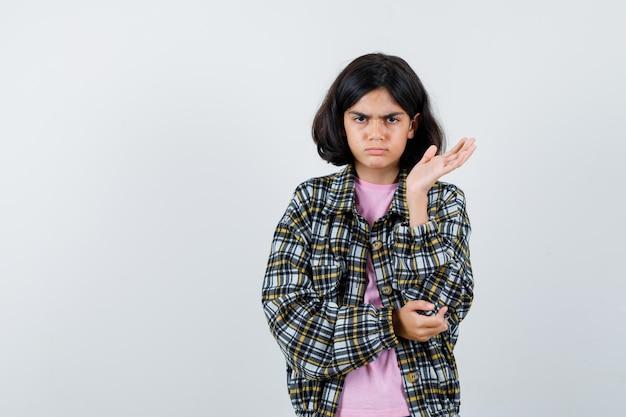 Preteen dziewczyna rozkłada otwartą dłoń na bok w koszuli, kurtce i wygląda na niezadowoloną. przedni widok.