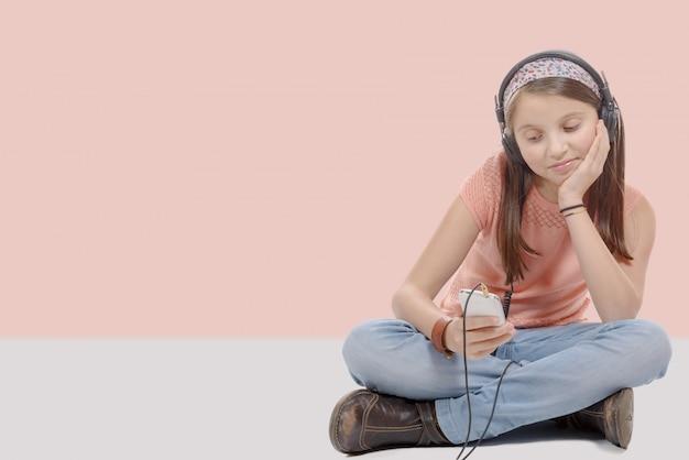 Preteen dziewczyna słucha muzyki ze swojego smartfona, siedzący ze skrzyżowanymi nogami