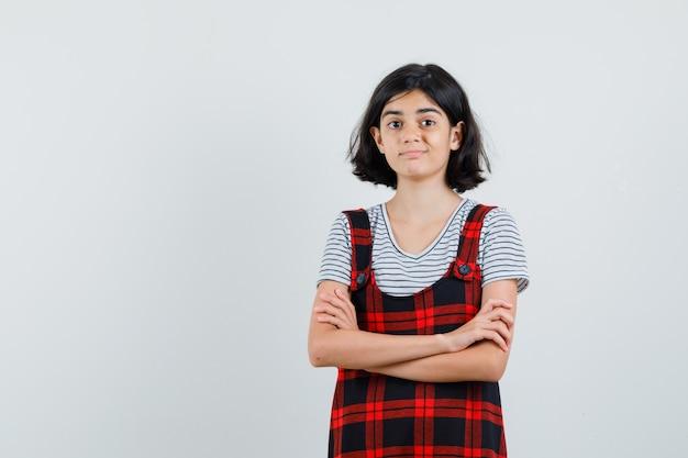 Preteen dziewczyna stoi ze skrzyżowanymi rękami w koszulce, kombinezonie i wygląda na zadowoloną. przedni widok.