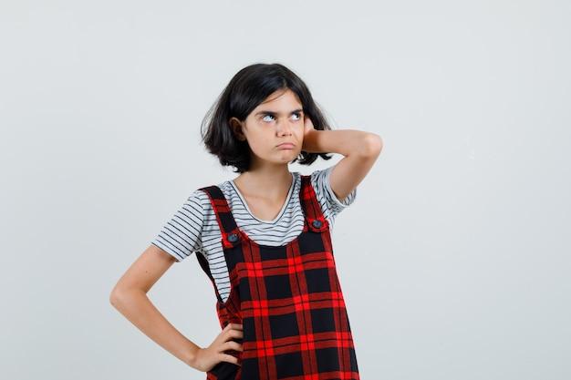 Preteen dziewczyna trzyma rękę na głowie, słuchając kogoś w koszulce
