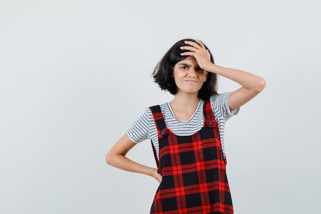 Preteen dziewczyna trzyma rękę na głowie w t-shirt