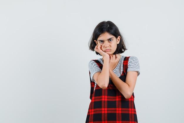 Preteen dziewczyna trzyma rękę na jej policzku w t-shirt