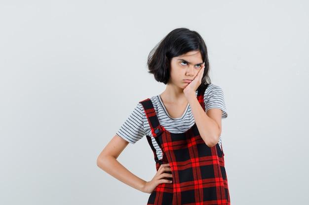 Preteen dziewczyna trzyma rękę na twarzy w t-shirt
