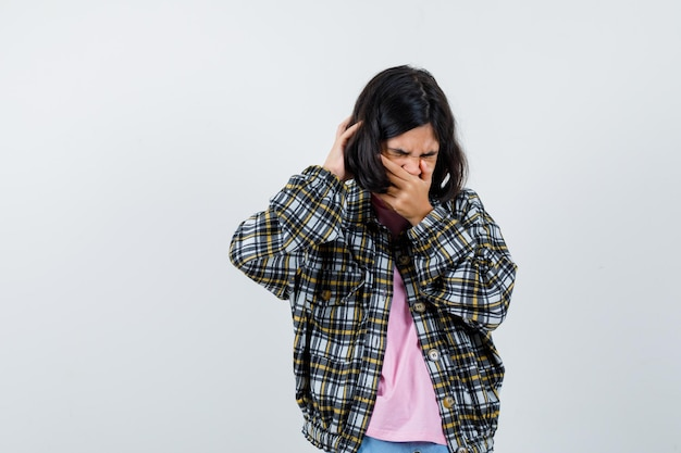 Preteen dziewczyna trzyma rękę na ustach podczas ziewania w koszuli, kurtce i wygląda na zmęczoną, widok z przodu.