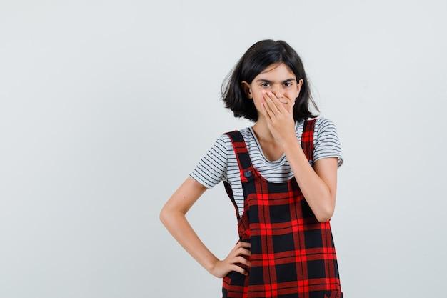 Preteen dziewczyna trzyma rękę na ustach w t-shirt