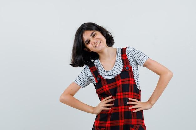 Preteen dziewczyna trzymając się za ręce na jej talii uśmiechając się w t-shirt