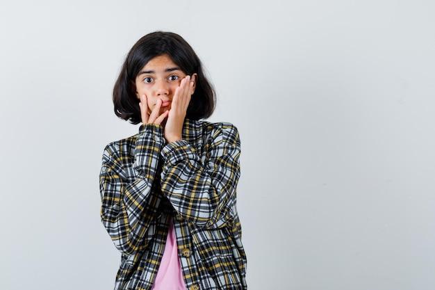 Preteen dziewczyna trzymając się za ręce na policzkach w koszuli, kurtce i patrząc podekscytowany. przedni widok.